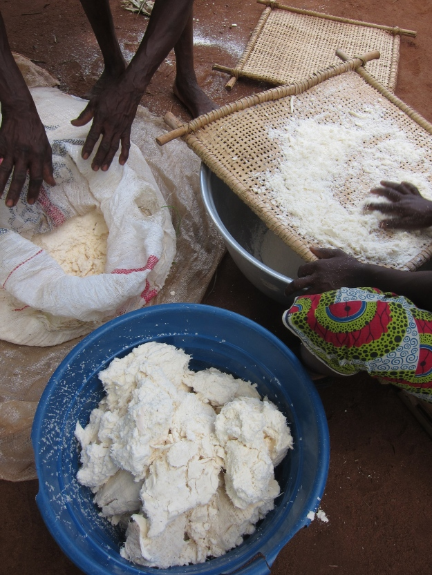 A sack and a bowl of pressed manioc, being sifted through screen to make gari.